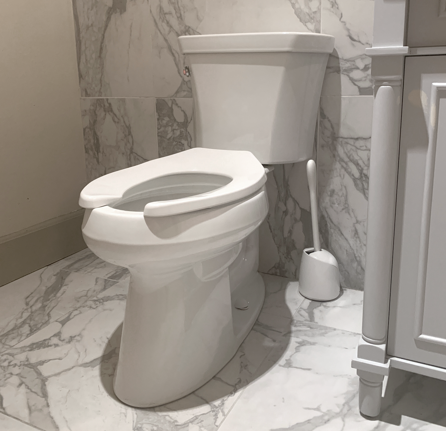 Toilet in Bathroom with Marble Floor and Walls