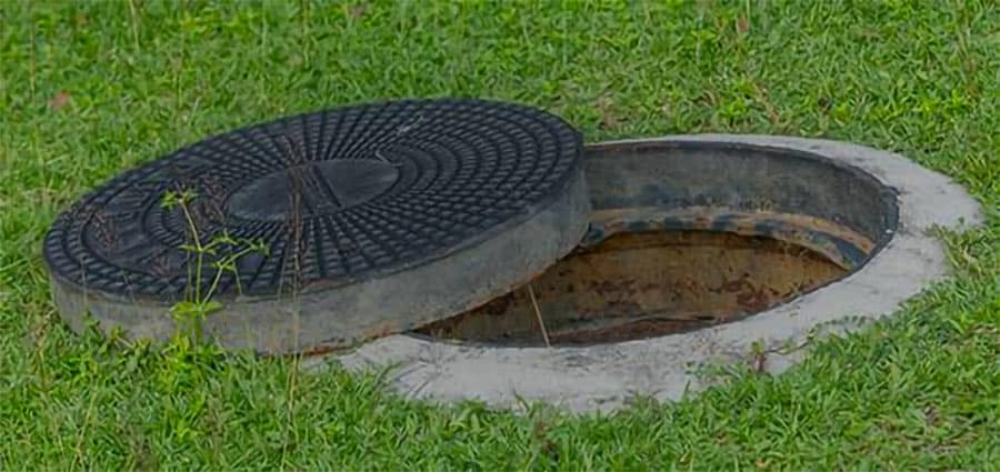 open manhole cover on lawn