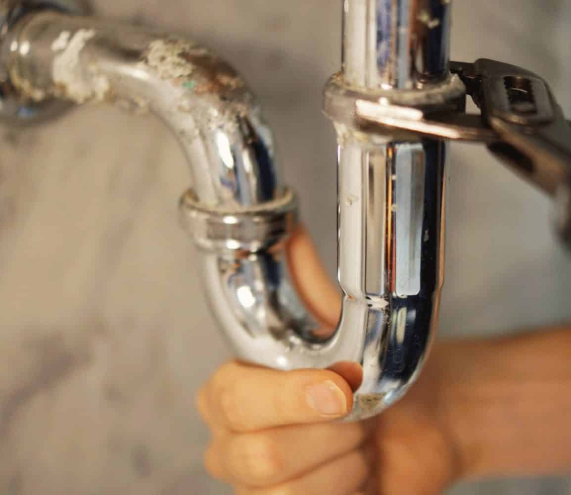 Plumber Repairing Pipe with Wrench